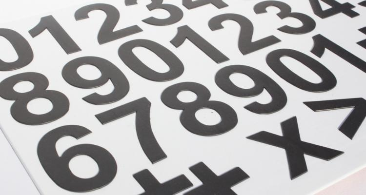 Czarne cyfry magnetyczne wraz ze znakami arytmetycznymi.