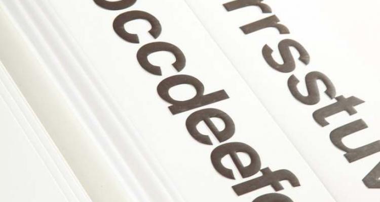 Widok na 5 cm małe literki położone na tablicach/kartach magnetycznych.